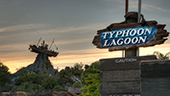 A life size sculpture of a shrimp boat impaled on a mountaintop stands in the background of a sign that reads Typhoon Lagoon