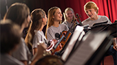 A group of teenagers with musical instruments smile while standing behind music stands in a studio setting