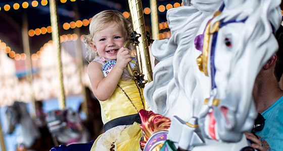 A toddler on Prince Charming Regal Carrousel at Magic Kingdom Park.