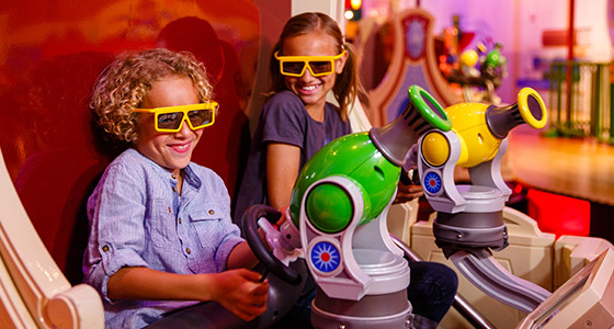 Two kids in 3D glasses on Toy Story Midway Mania! at Disney's Hollywood Studios Park.