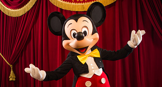 Mickey Mouse stands onstage wearing a music conductor costume