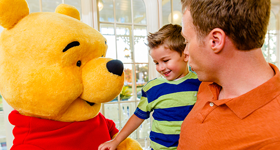 A father holds his preschool-aged son who smiles during a Character greeting with Winnie the Pooh