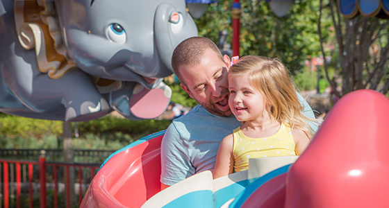 A father enjoys a ride on Dumbo The Flying Elephant as his preschool-aged daughter sits on his lap