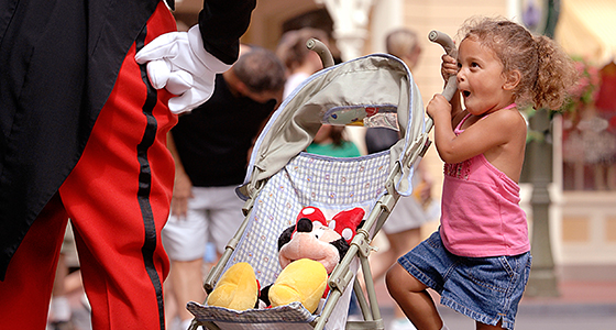 Mickey Mouse rests his hands on his hips while meeting an preschool-aged girl grasping her stroller