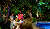 Two women with drinks talk while standing at an outdoor cocktail table near a candlelit stone path