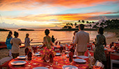 A group of Guests stand on a beach near banquet tables set for an elegant outdoor dinner