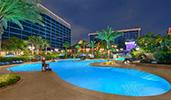 A large, asymmetrical pool behind the Disneyland Hotel