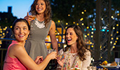 Three young women share cocktails and appetizers at an outdoor restaurant