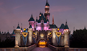 Lights illuminate Sleeping Beauty Castle in Disneyland Park at sunset