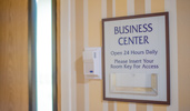 A sign posted on the wall reads Business Center Open 24 Hours Daily