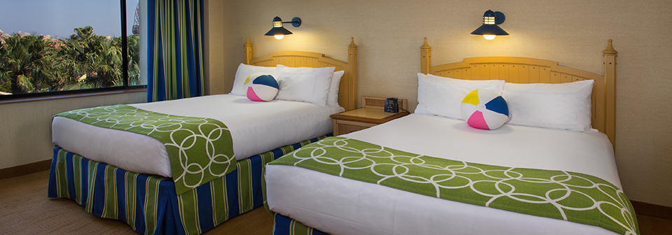 A queen size bed and a double bed with striped dust ruffles in a room with a window looking out on palms