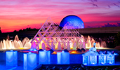A chef sets up buffet and drink stations in front of a fountain with a pyramid sculpture design
