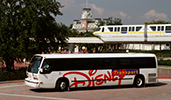 A Disney Transport shuttle bus drives past a monorail track