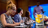 A woman works on her tablet as 2 coworkers talk to a man at a conference table