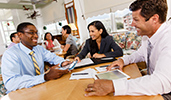 Business colleagues work together in small group at tables in a casual meeting area