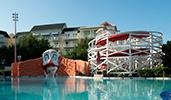 A pool with a waterslide has a Boardwalk carnival clown motiff