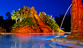 The Lost City of Cibola pool illuminated at night with a fountain, railings and a 50 foot pyramid with palm trees, stone steps and more