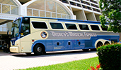A Disney's Magical Express bus waits in front of a hotel entrance
