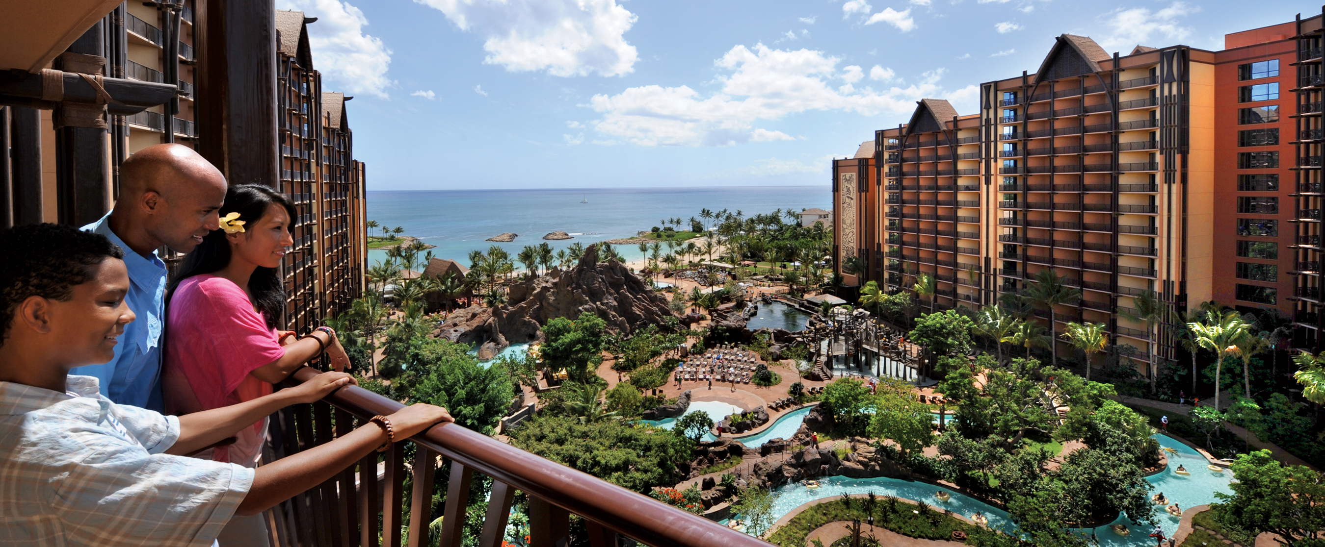 A family looks over the balcony at the Aulani pool area