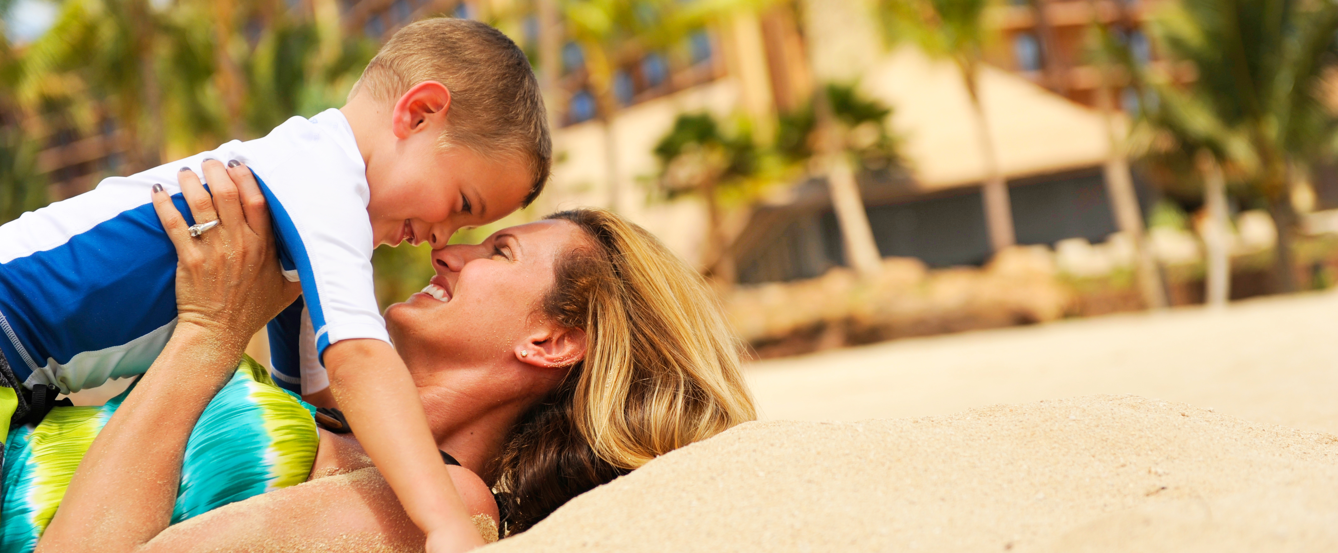 A mom plays with her son at the beach
