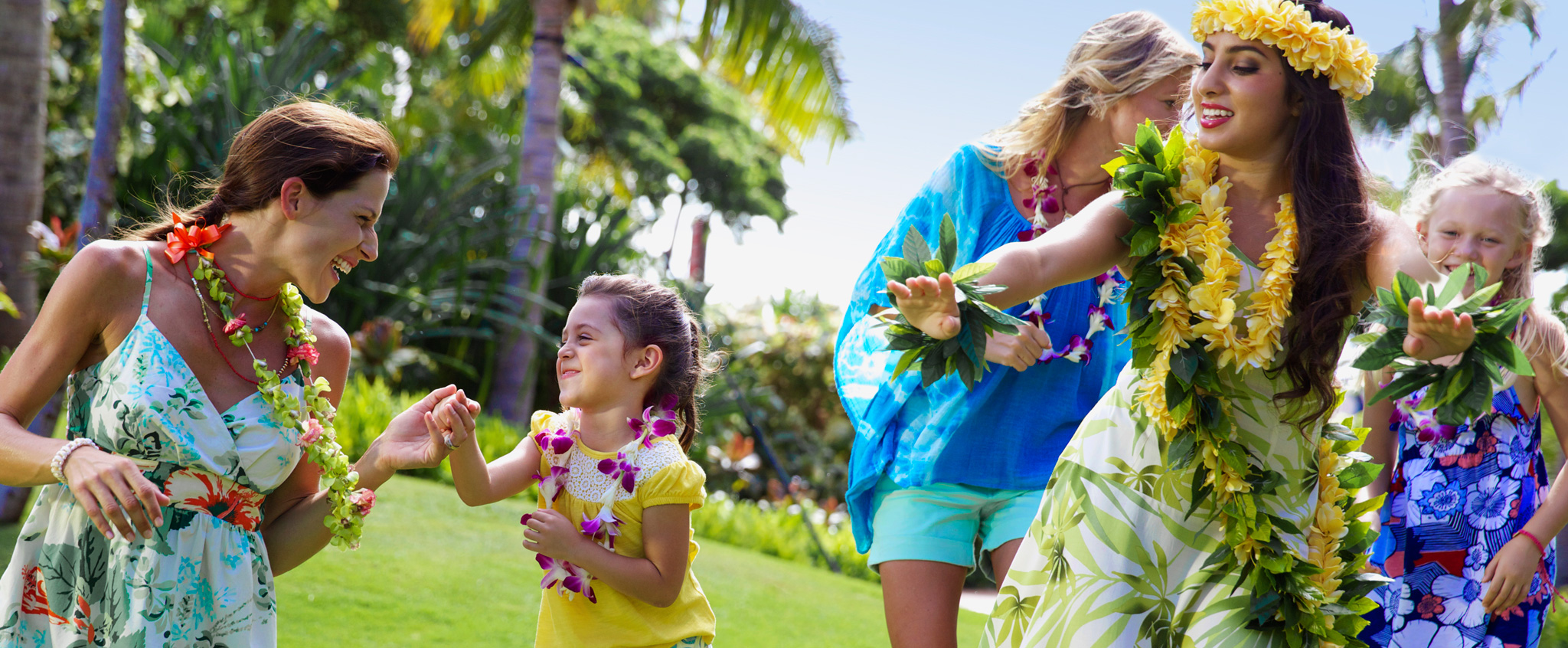 Two young girls and their mothers wearing flower leis follow along during a Hawaiian hula dancing lesson