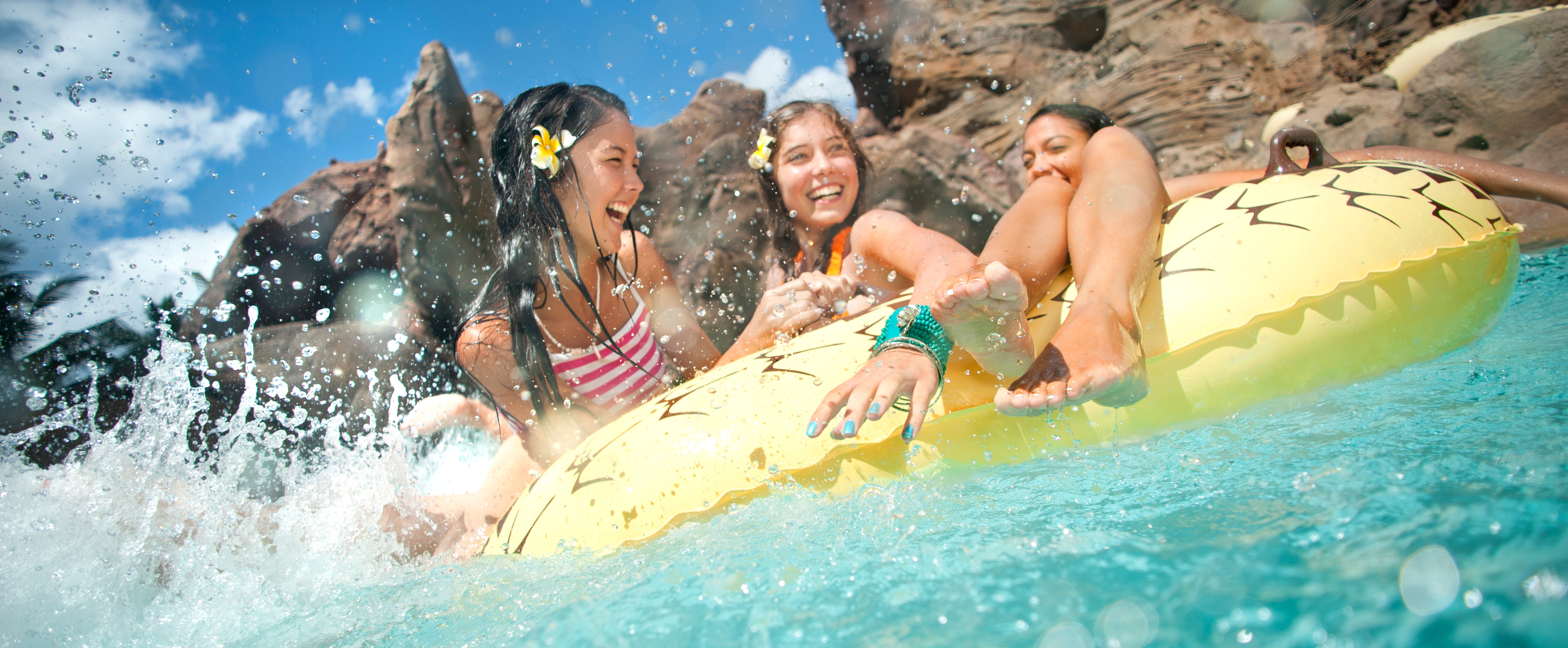 Girls float on an inner tube in the Aulani pool area