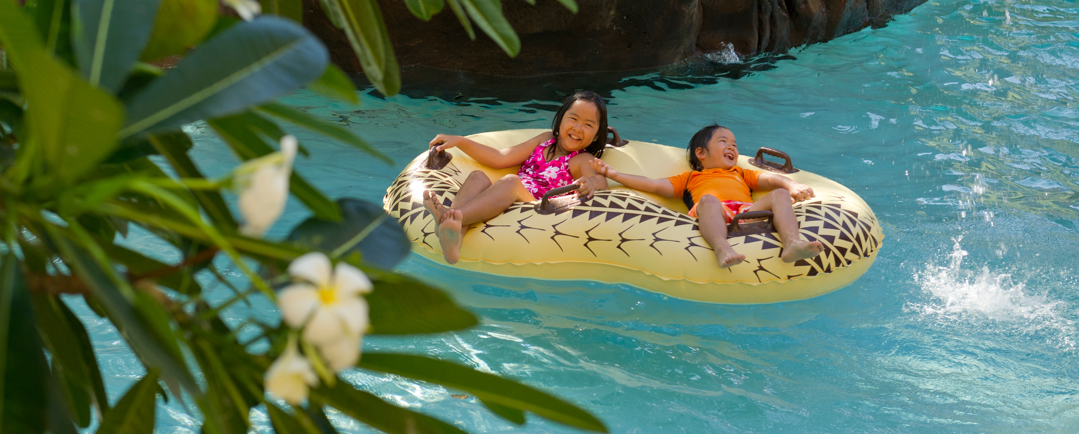 Children floating in a 2-person tube on the lazy river at Aulani