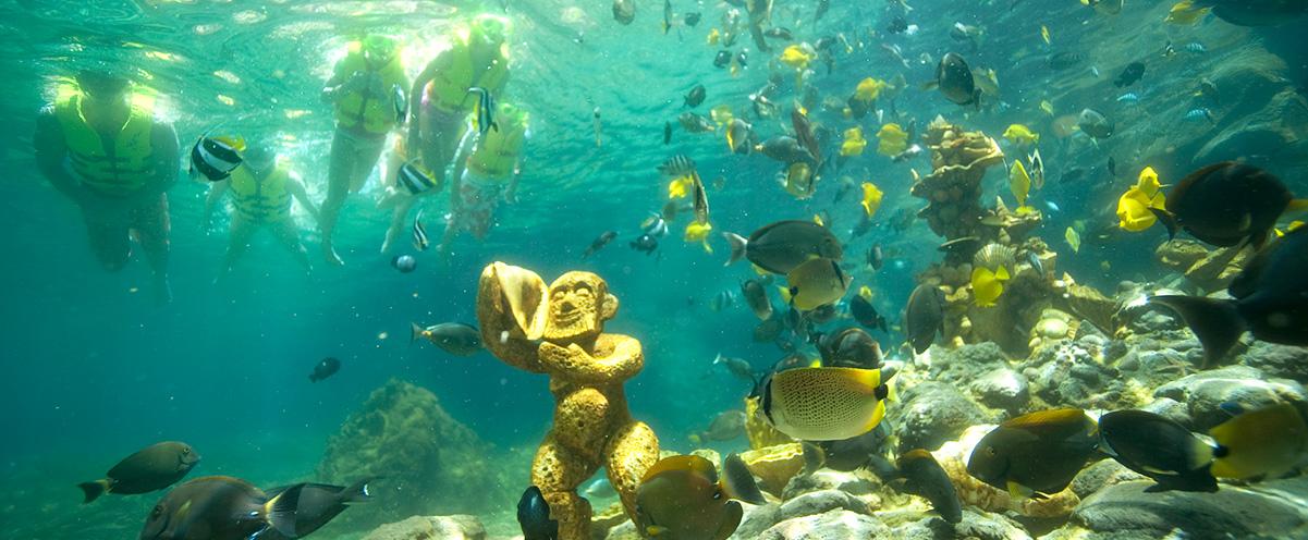 Tropical fish, snorkelers and Menehune at Rainbow Reef lagoon