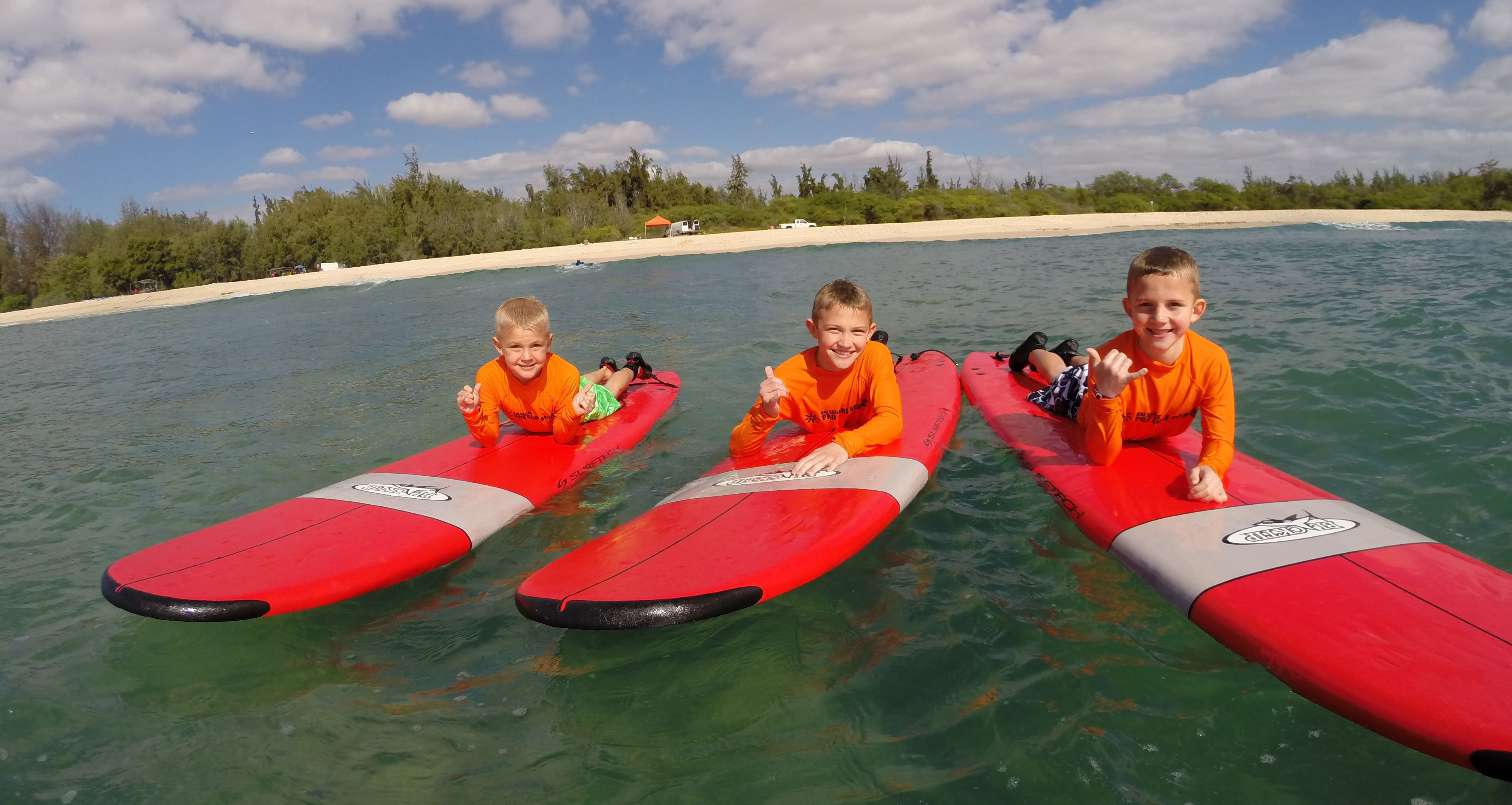 Three young boys give the hang loose hand sign as they lie on their bellies on surfboards floating in the ocean