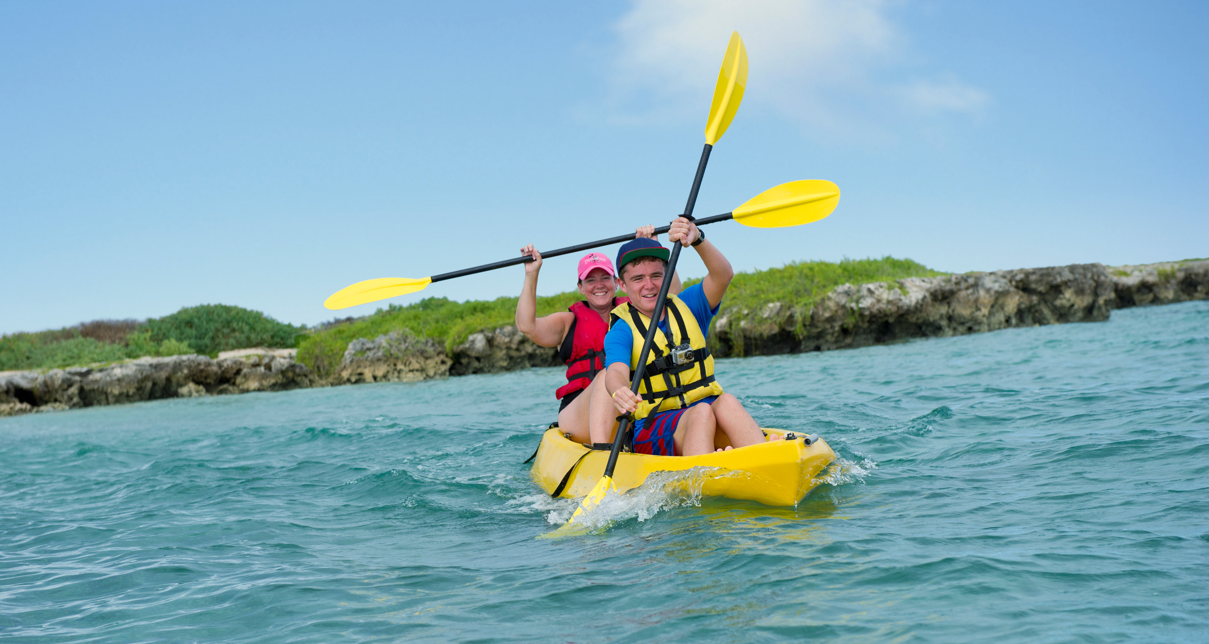 A couple paddles a kayak through the water with a rocky shore in the background