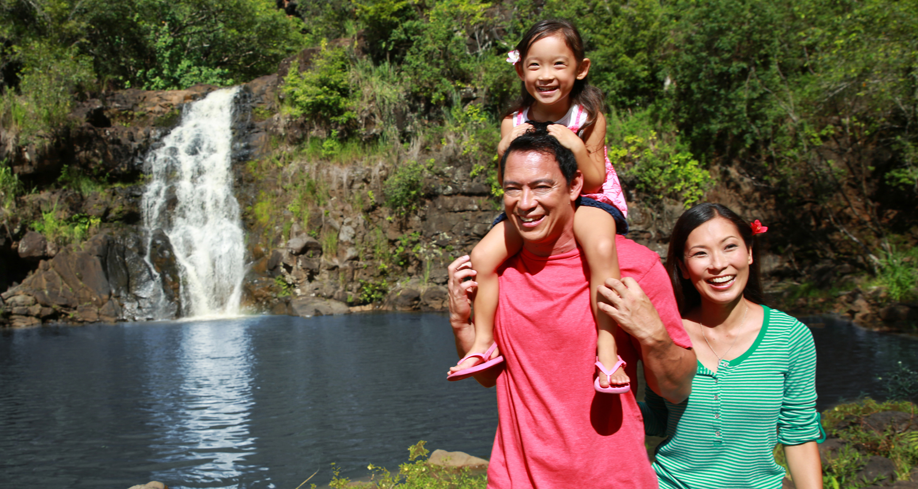 A woman and a man with a young girl on his shoulders walk beside a pond with a waterfall in the background
