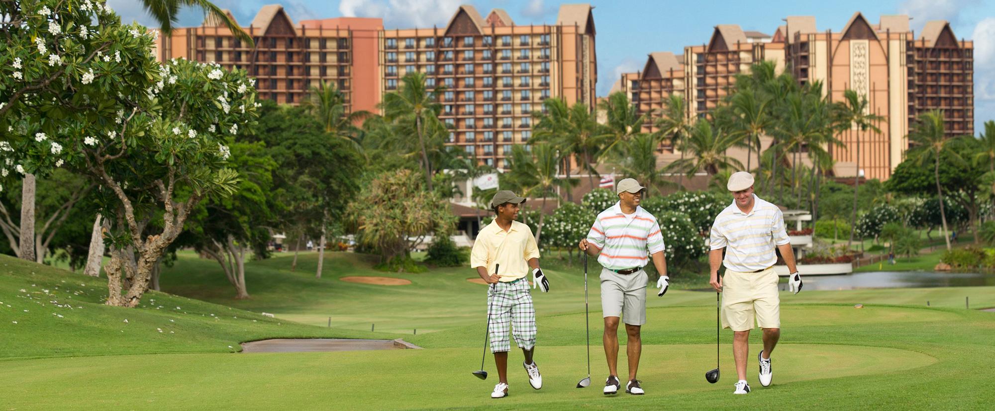 Three men in golf attire walk across the green, each carrying a golf club