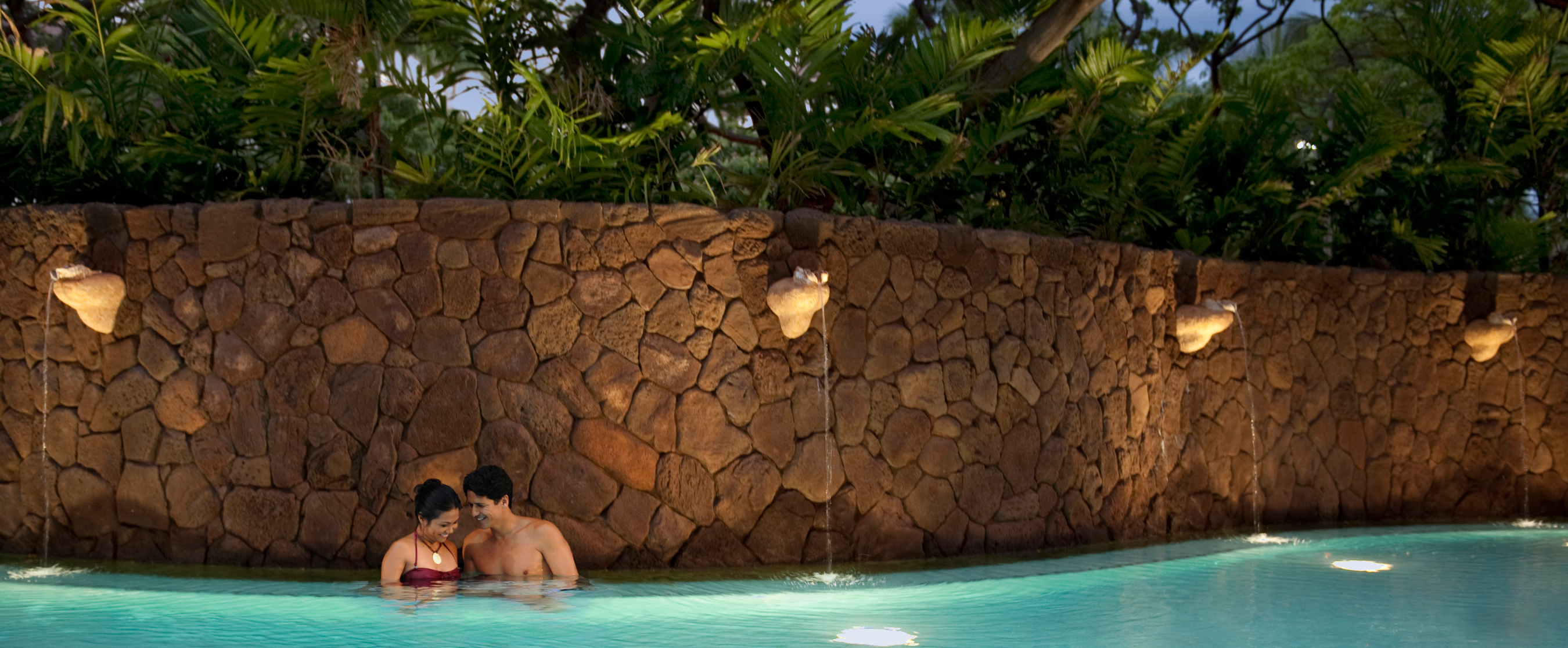A couple shares a laugh as they stand together in the adults-only Wailana pool at Aulani Resort and Spa