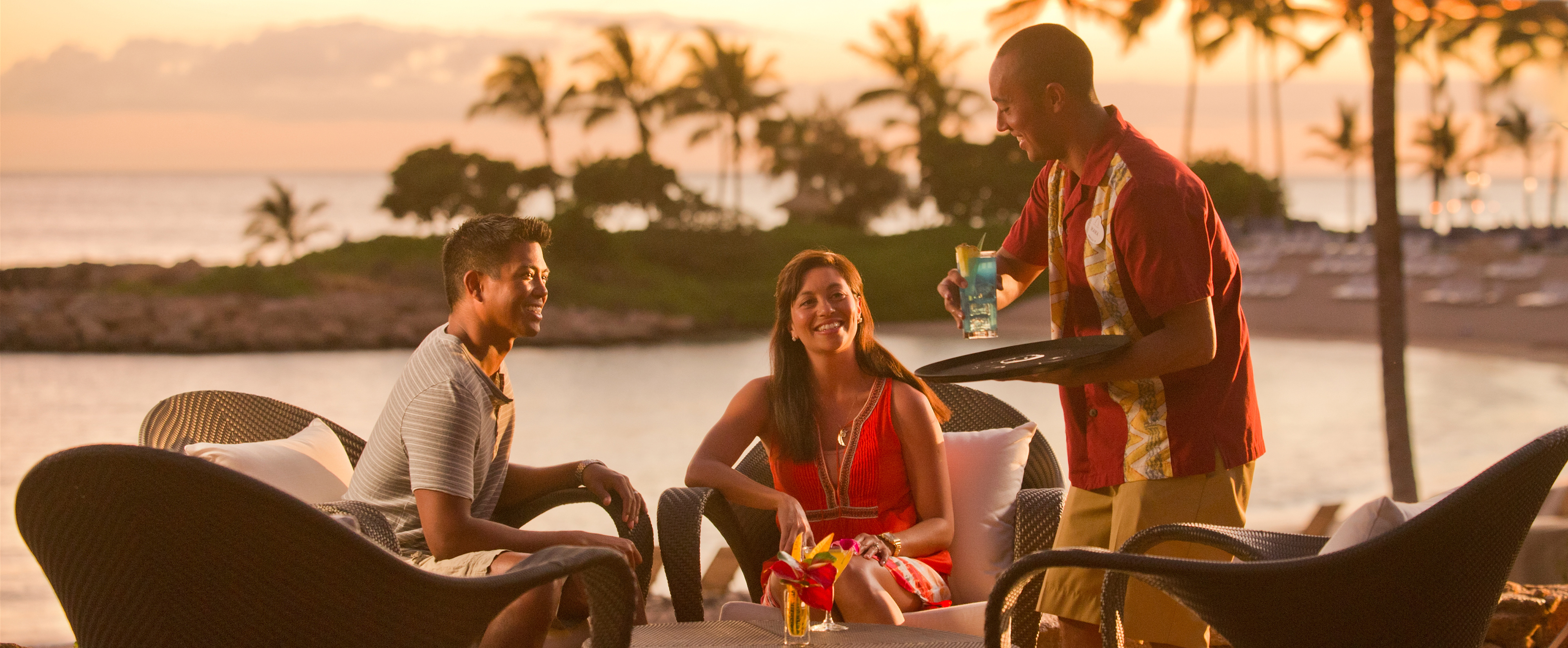 A waiter serves drinks to a couple seated on the outdoor patio at Ama Ama restaurant at Aulani Resort and Spa