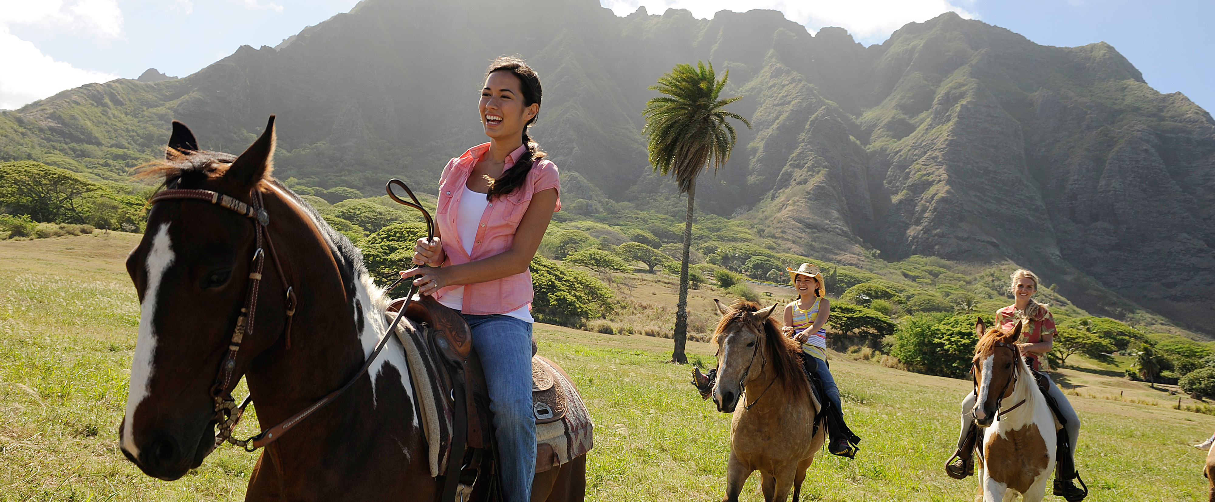 Two women and a girl ride horses across a Hawaiian meadow with lush hills in the background