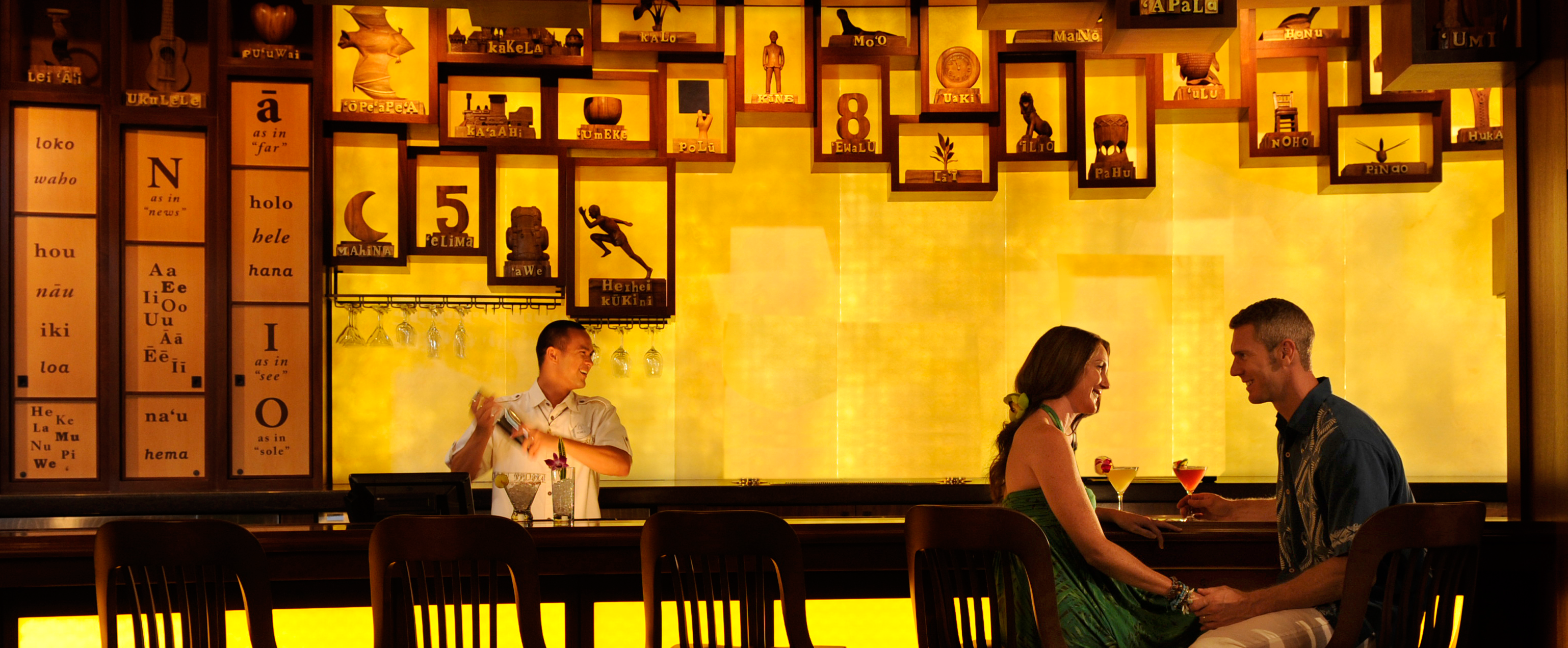 In a stylish bar, a young couple sits hand in hand gazing into each other's eyes while a bartender mixes a drink