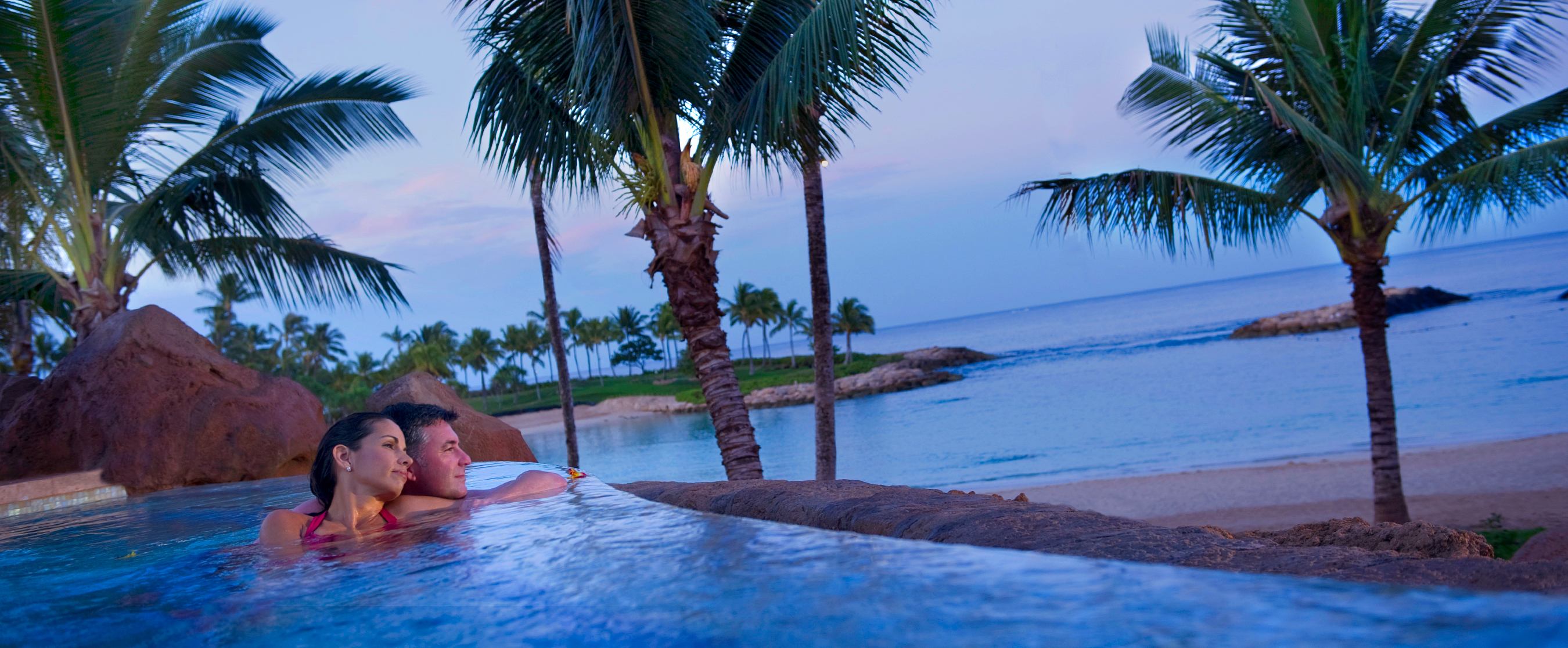 With the beachfront in the background, a couple lounges together in the adults only whirlpool spa at Alohi Point of Aulani Resort and Spa