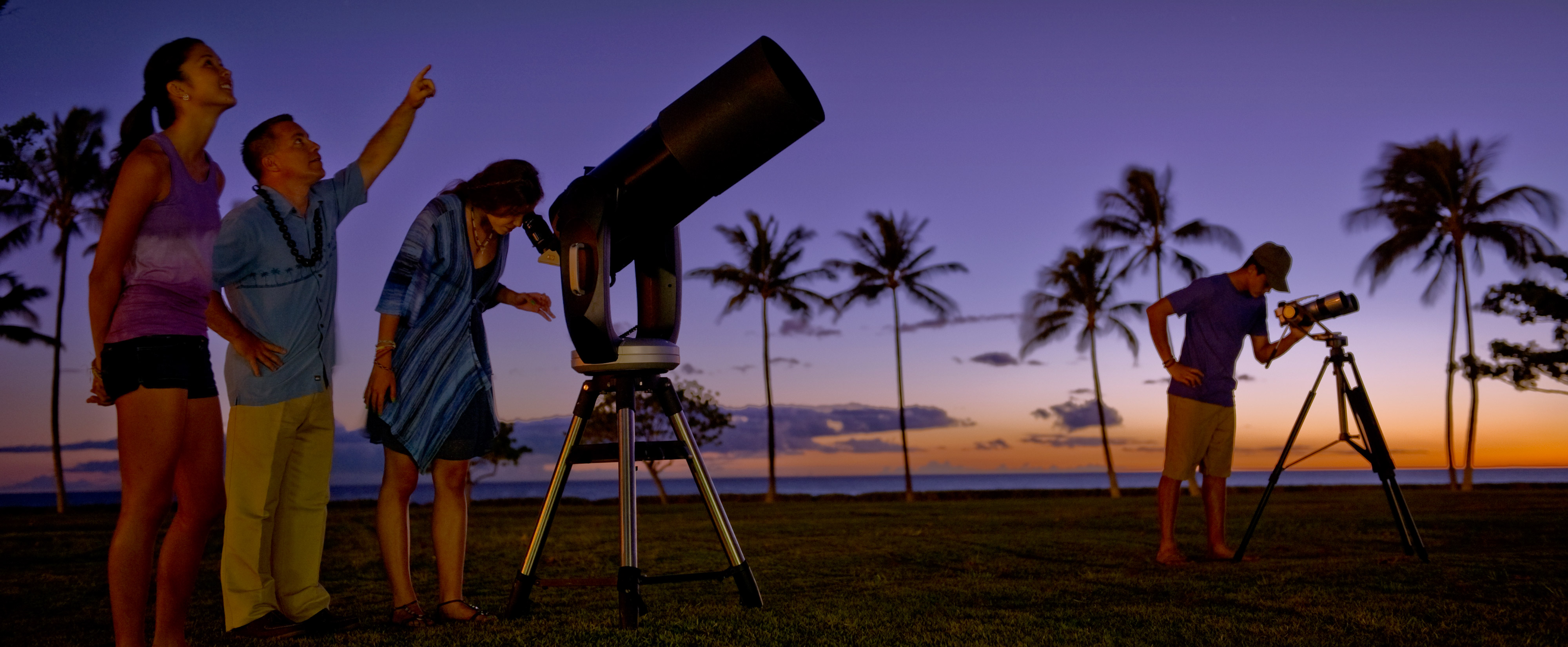 A Cast Member speaks and points skyward as a young woman listens and another looks through a large telescope