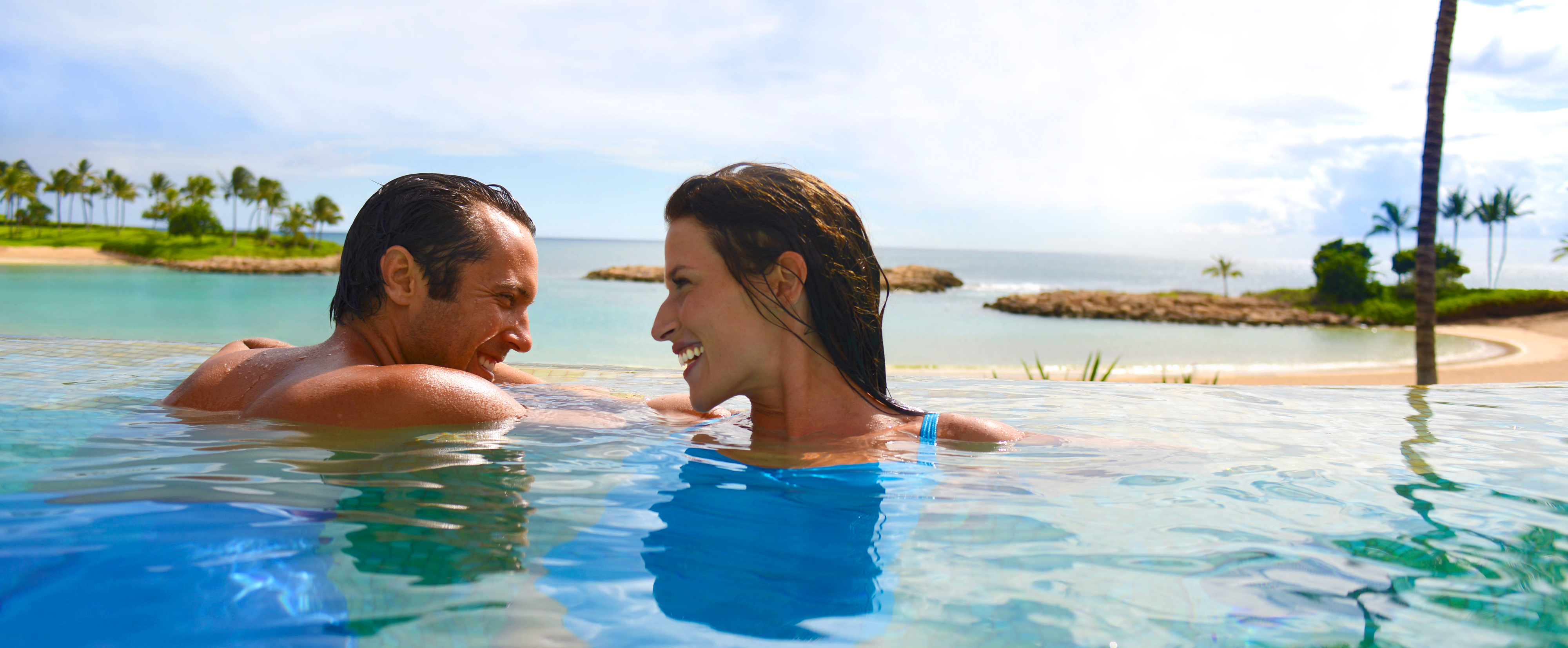 A young couple laughing together while relaxing in the water of the Ka Maka Grotto oceanfront pool