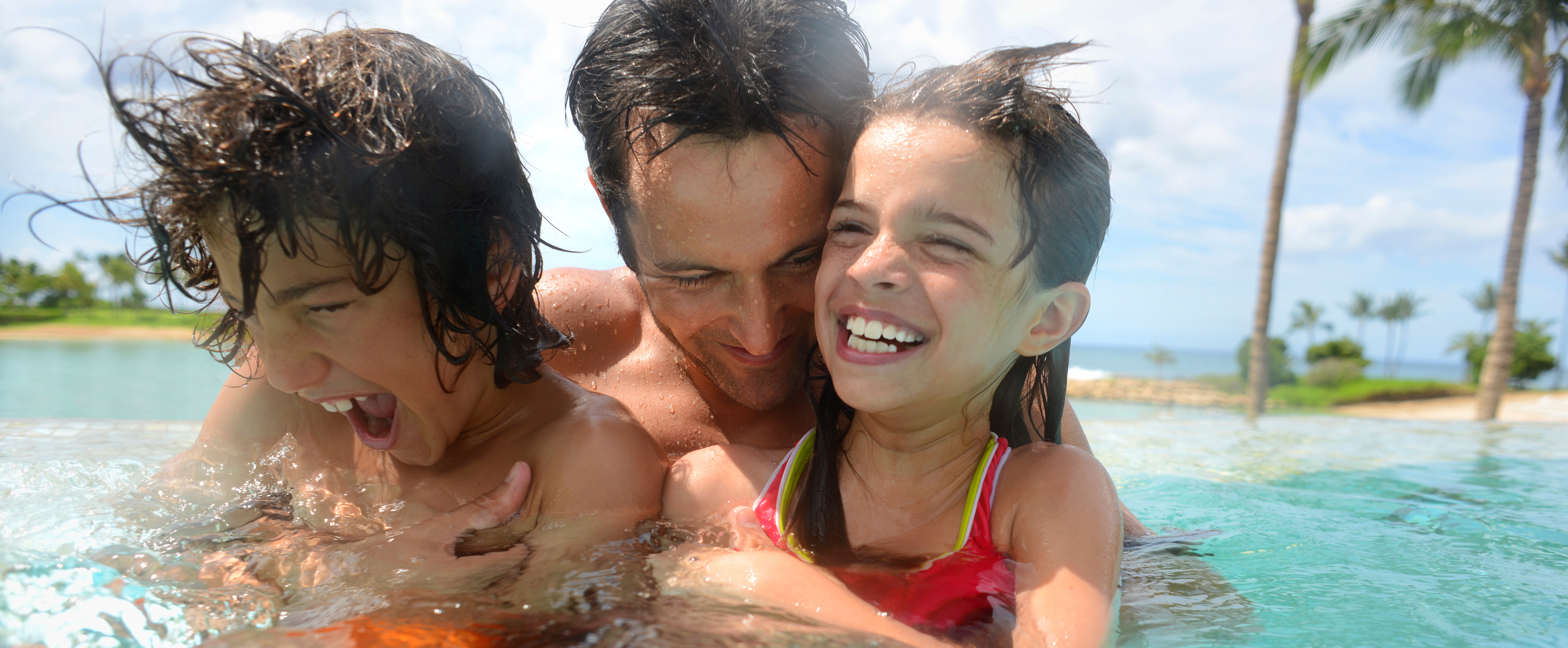 A dad laughs with his son and daughter while splashing around in the Ka Maka Grotto oceanfront pool