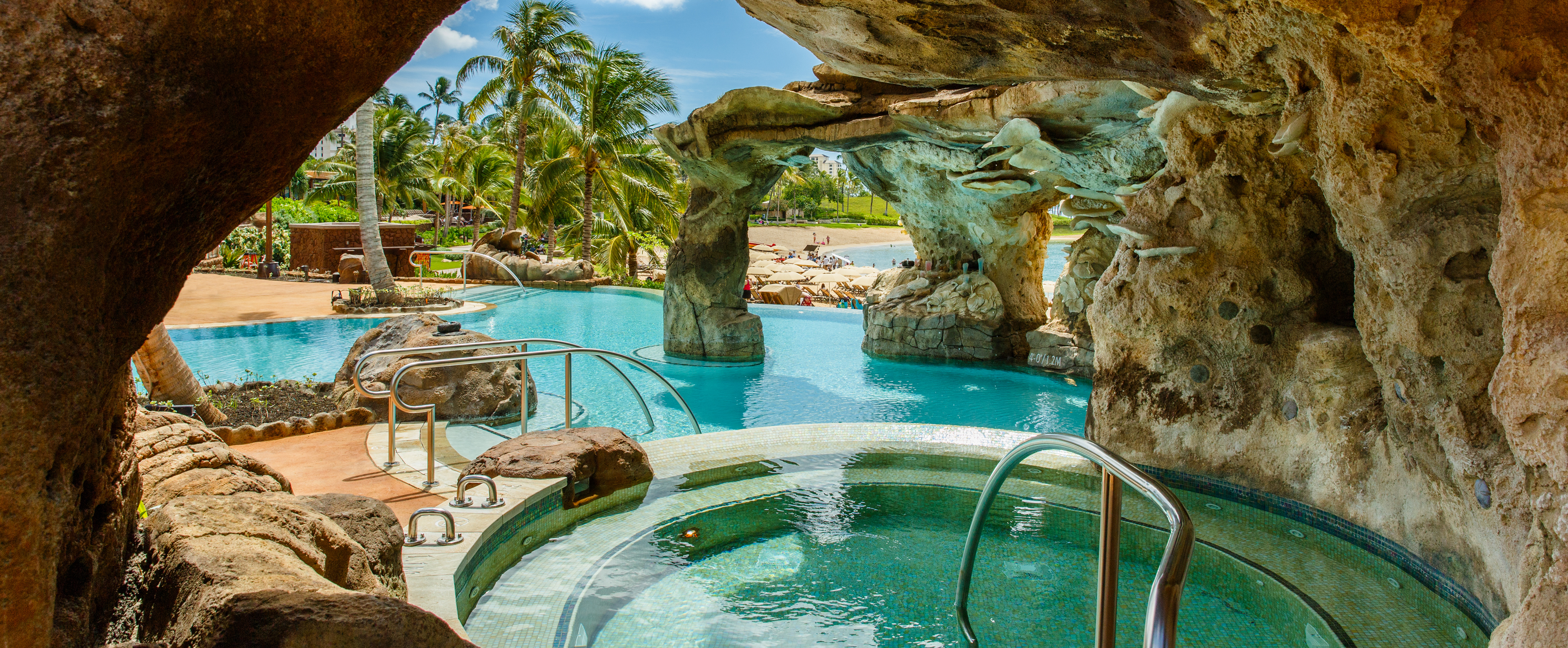 A rocky outcropping surrounds a hot tub that leads into the waters of Ka Maka Grotto oceanfront pool