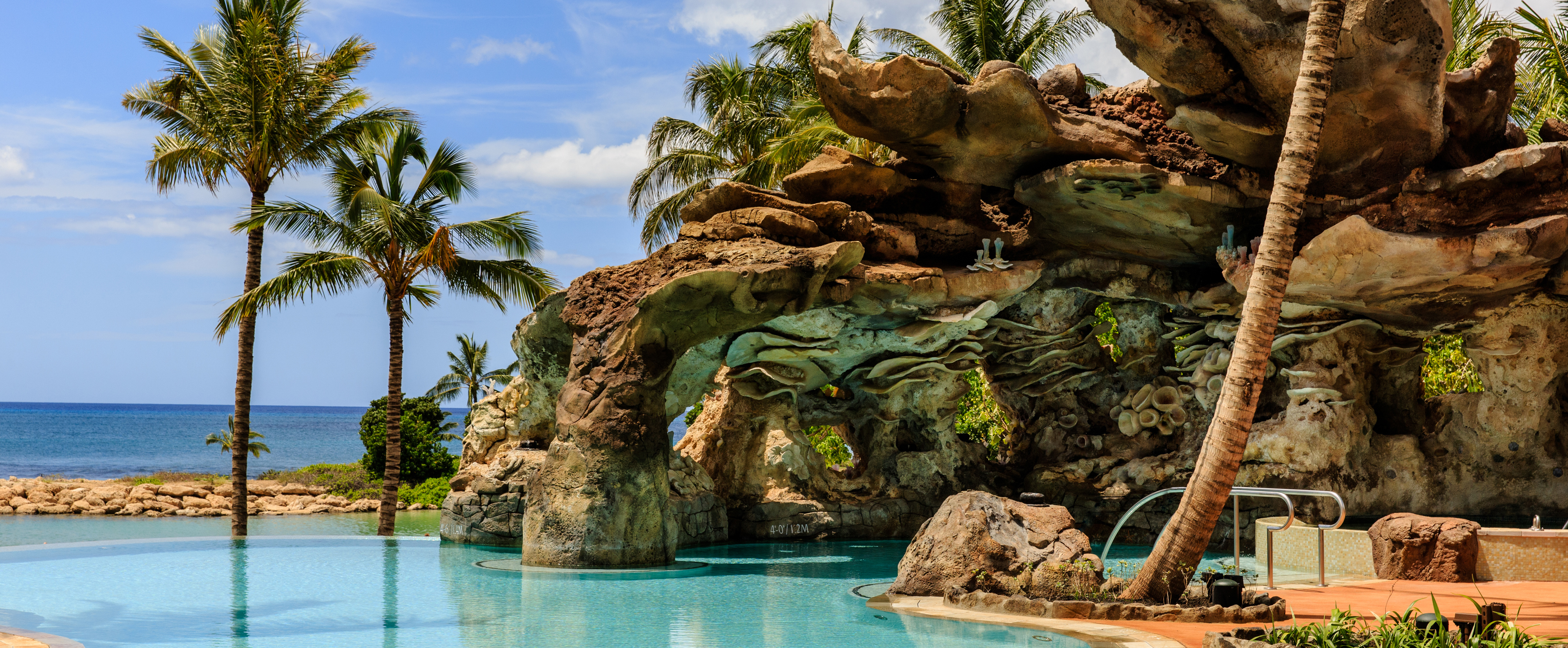 ocean themed outcropping and several palm trees surround the ka maka grotto