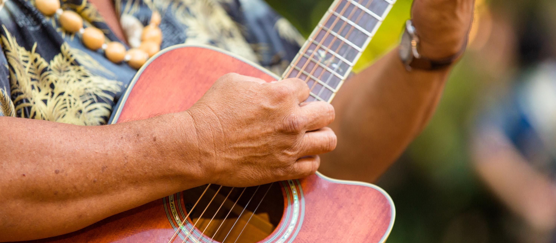 A hand gently strums a guitar