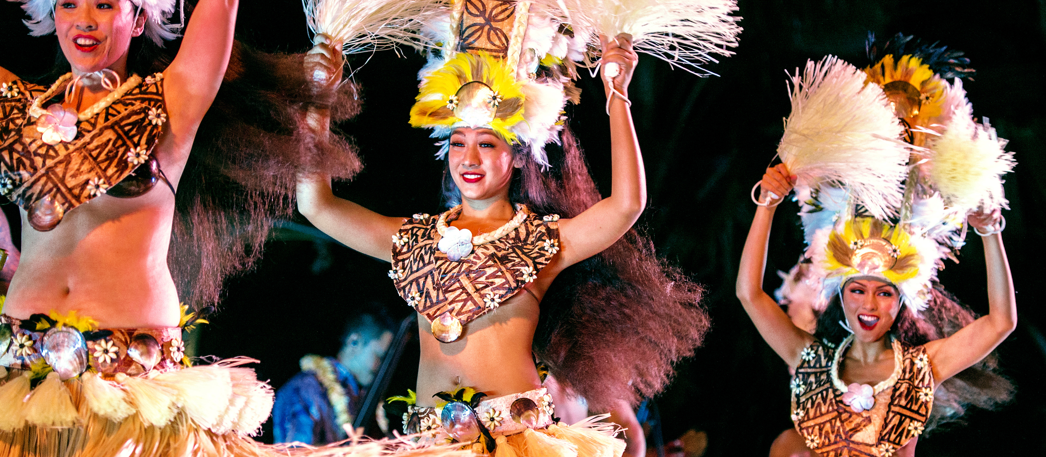 Hawaiian dancers in grass skirts and tall head dresses made of feathers, wave grassy pom-poms while performing a traditional dance at the Ka Wa'a Luau.
