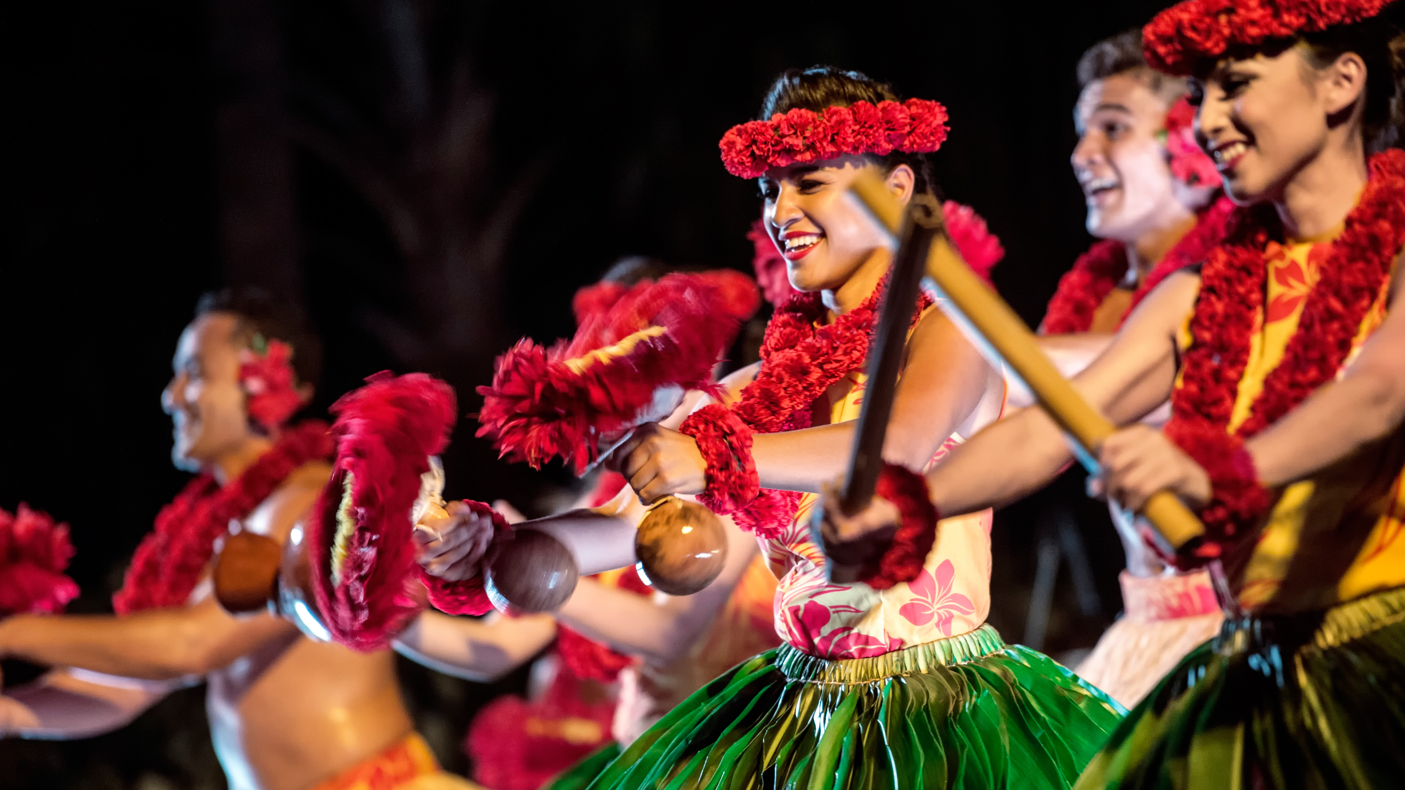 At the Ka Wa'a luau, 2 female performers wearing hula dresses and floral headbands beat out rhythm on sticks