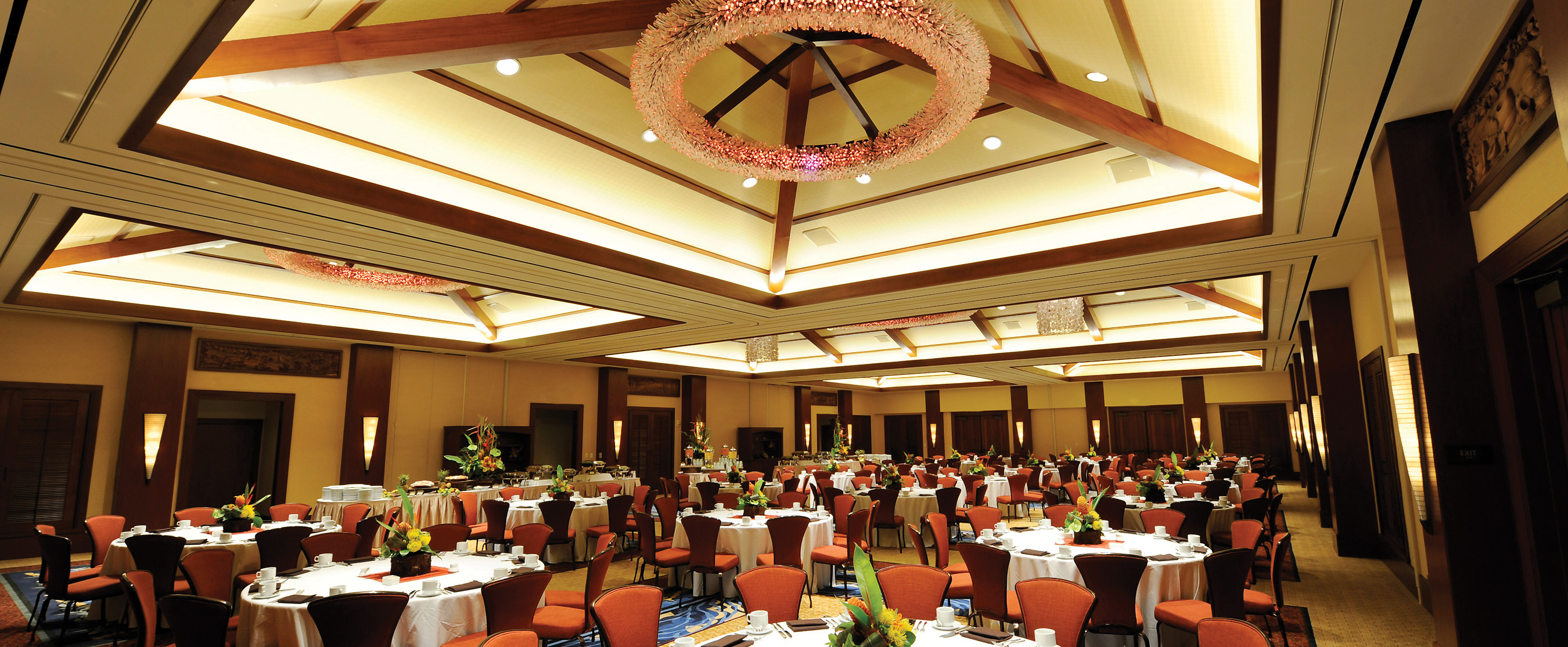 A ballroom with dining tables and chairs set up to host a buffet meal