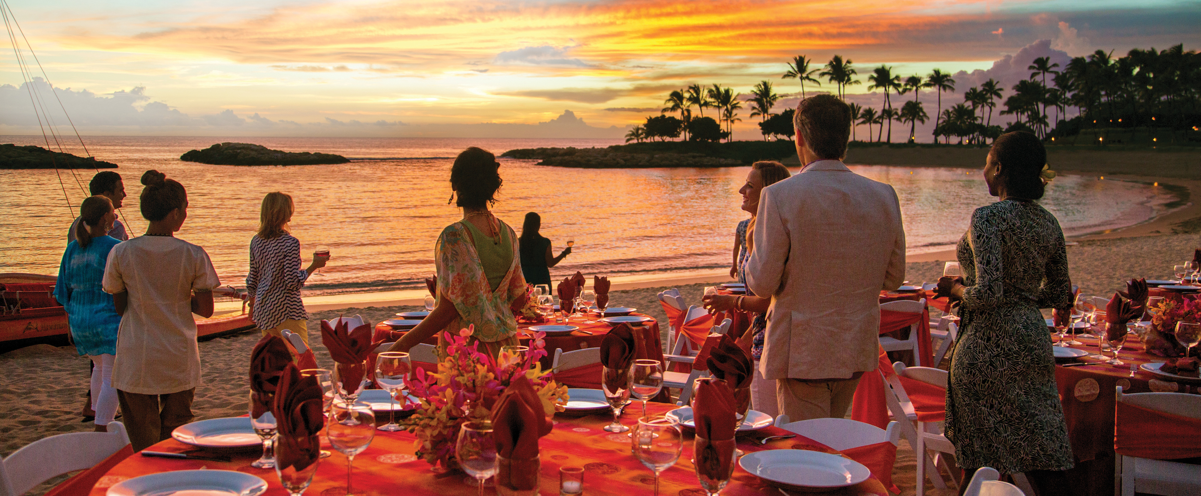 Party goers on the beach pause to admire a colorful sunset over the lagoon