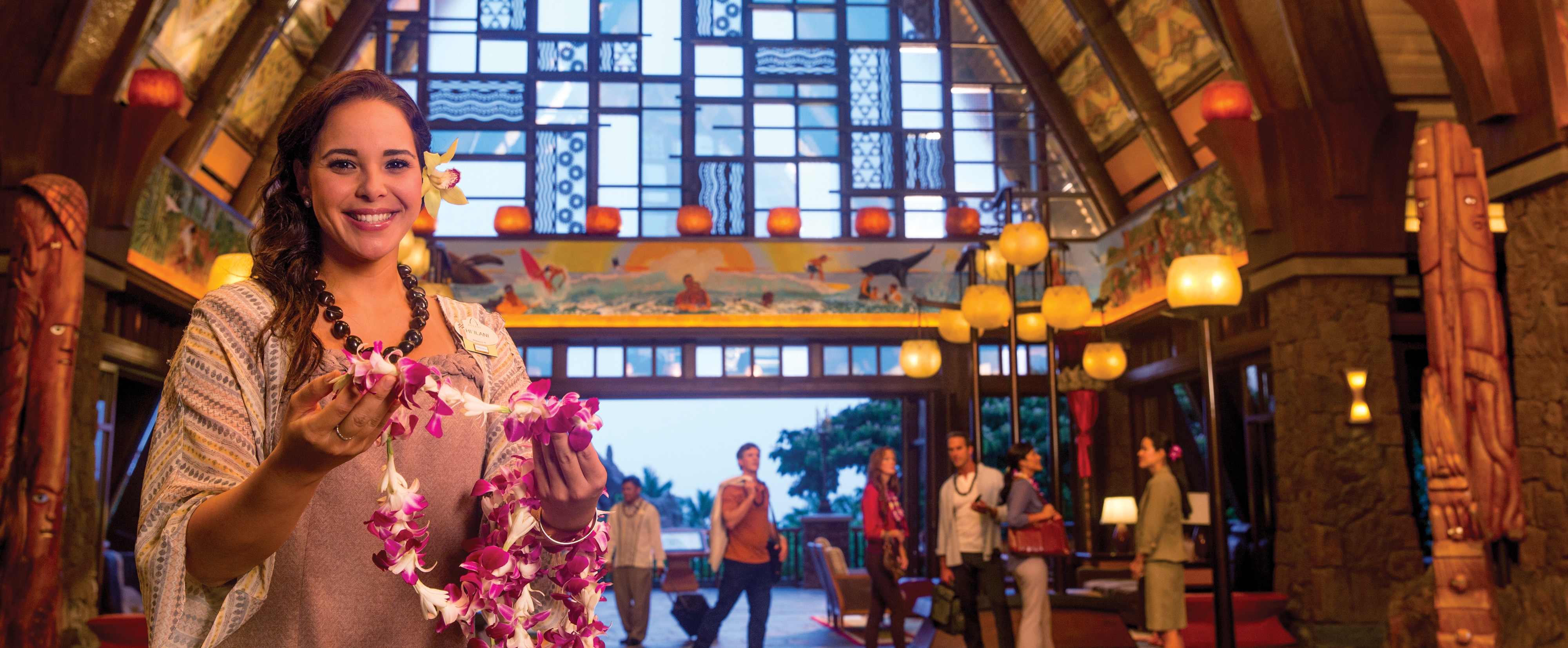 A smiling woman stands in the Aulani hotel holding out an orchid lei
