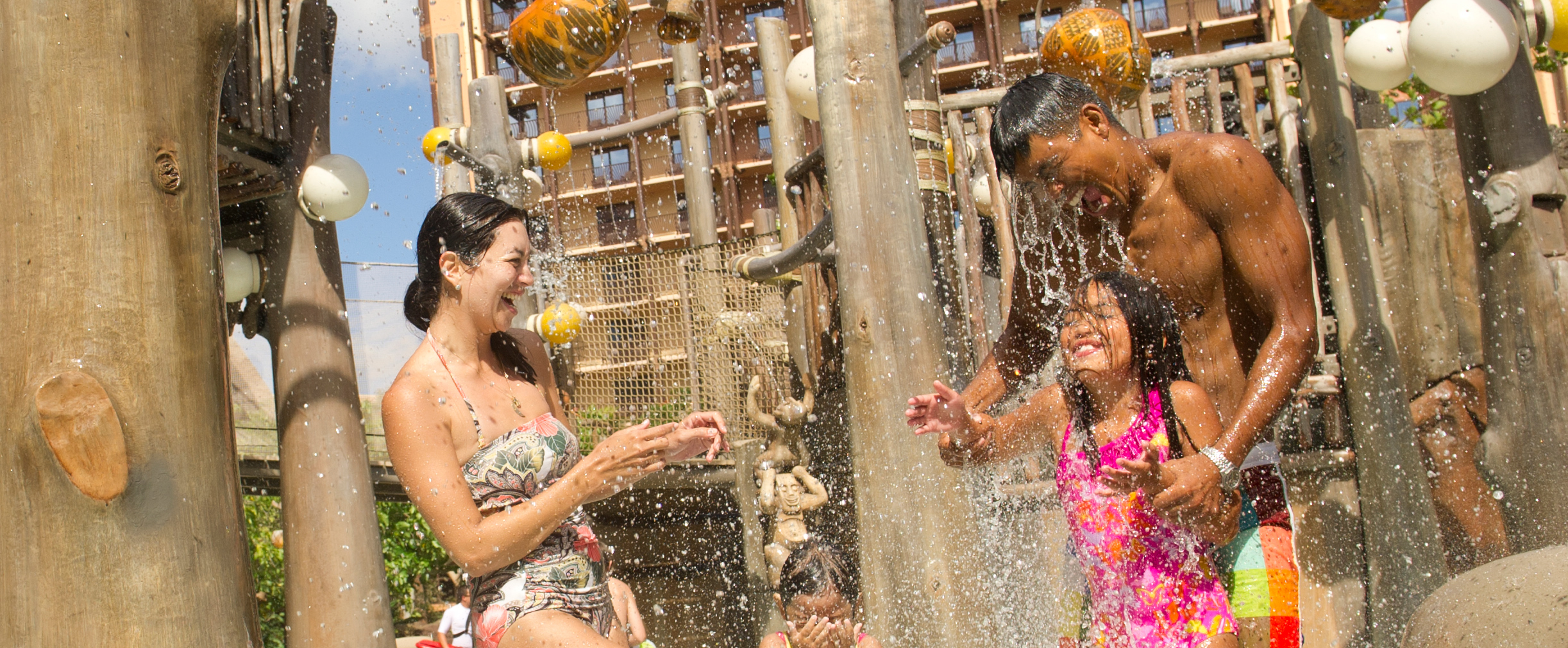 A mother laughs while water spills onto her husband and daughter from the Menehune Bridge play area