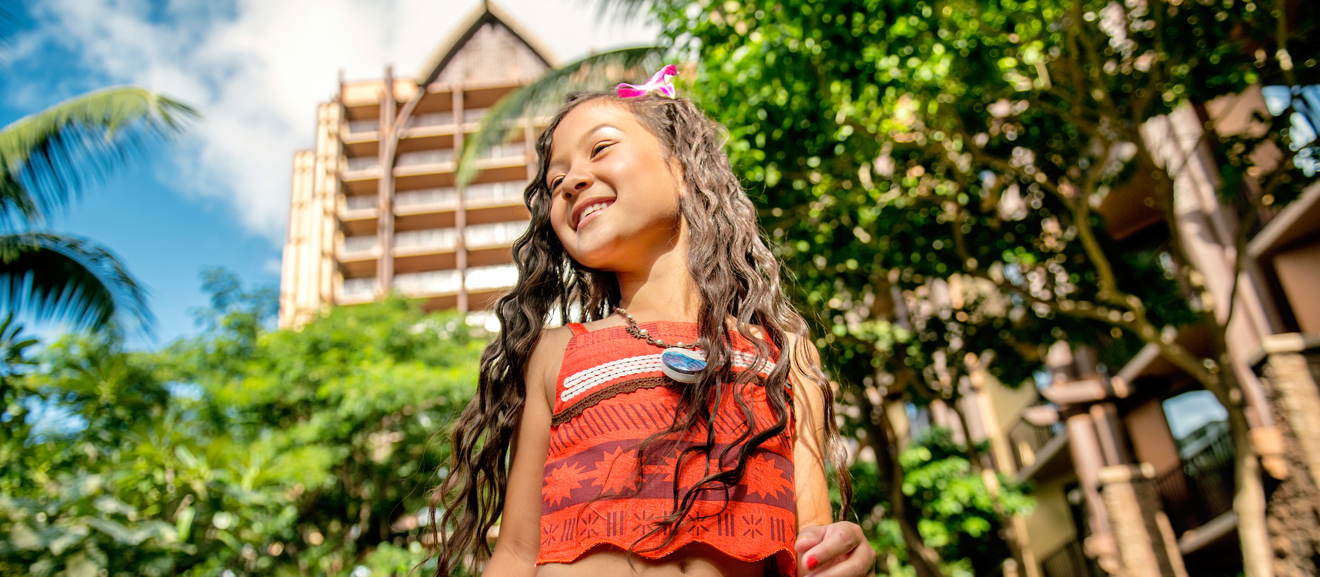 A young girl stands in front of Aulani and shows off her Moana transformation, complete with a tropical flower in her wavy hair, top with island prints and necklace with a seashell charm.